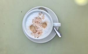 Cappuccino im Häferl auf grünem Tisch